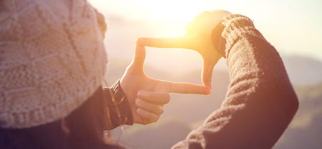 Foto van een vrouw die een doorkijk maakt naar de zon met haar handen - Maria Menger